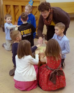 Margot and kids doing a music activity during First Hour.